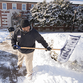 workers scrape snow from path