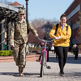 David Chambers helps Jordan Fadness push her bicycle across campus after class at ECU on Tuesday afternoon. (ECU Photo by Rhett Butler)