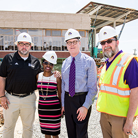 Dr. Erik Kneubuehl, Dr. Virginia Hardy, Chancellor Cecil Staton and Aaron Lucier pause for a photograph outside of ECU's new student center after a tour.