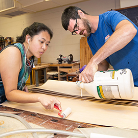 Psychology and anthropology major Chisty Vang and ECU instructor Judd Snapp glue together thin layers of wood as they make a skateboard during a woodworking class.