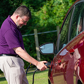 Aaron Lucier plugs his car into a EV charger on College Hill.