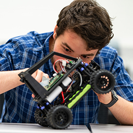 A student works on a remote-controlled car that was built in class.