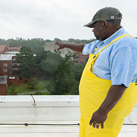 While checking campus roofs after Hurricane Florence, Monuel Purnell stands on the Science and Technology building and looks at Howell.