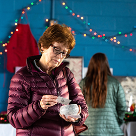 Pat Larsen looks at a piece by ceramic artist Kelsey Lineberger during the Annual Holiday Art Sale at A Time For Science on Dickinson Avenue.