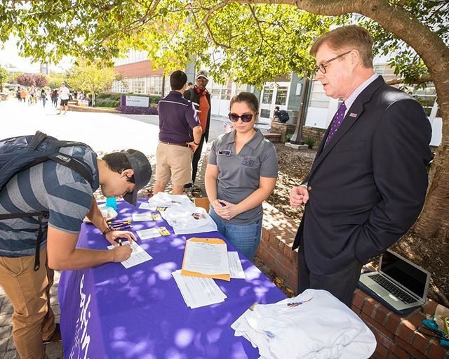 Chancellor Staton, right, and Kari Carr, center, watch a student donate Pirate Bucks to hurricane relief in Florida and Texas. (ECU photo by Cliff Hollis)