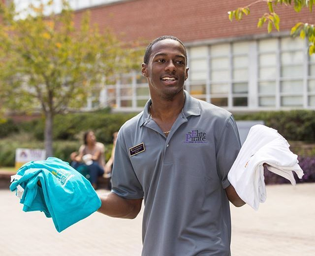 Markus Mosley holds up t-shirts that students get when they donate $10 worth of Pirate Bucks to hurricane relief in Florida and Texas. (ECU photo by Cliff Hollis)