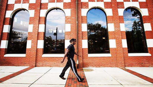 An ECU student walks past the Todd Dining Hall on College Hill on Wednesday afternoon. (ECU Photo by Rhett Butler)