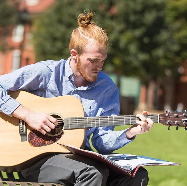 Cody Braxton sits on the mall playing his guitar in the afternoon sun. (ECU Photo by Cliff Hollis)