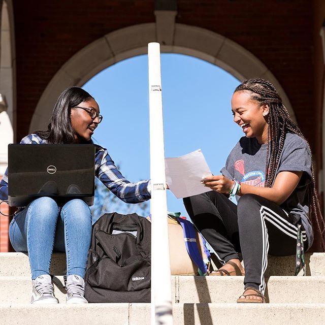 ECU students Grace Kelly, left, and Oprah Whitfield laugh as they talk about a paper Kelly is writing for a Human Development course while setting on the steps near Wright Auditorium on Wednesday afternoon. (ECU Photo by Rhett Butler)